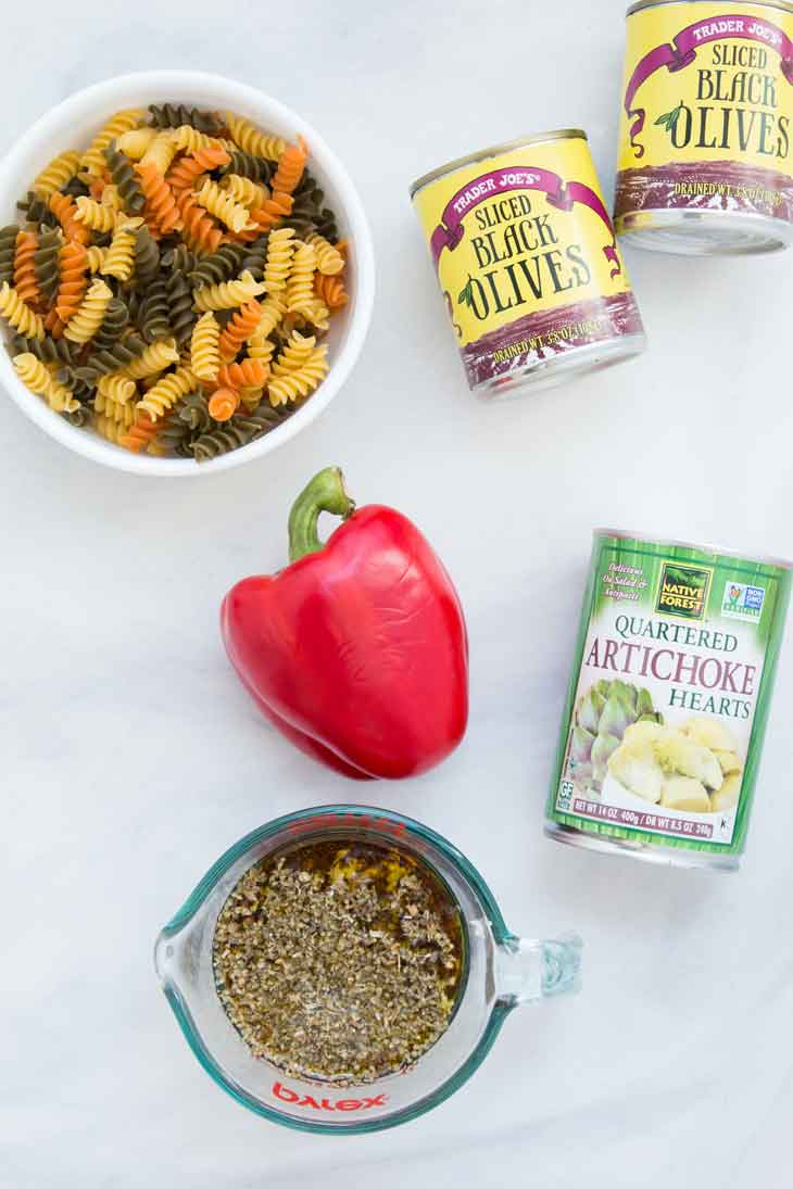 The ingredients for an easy pasta salad recipe. Pasta, peppers, dressing, artichoke, and olives!