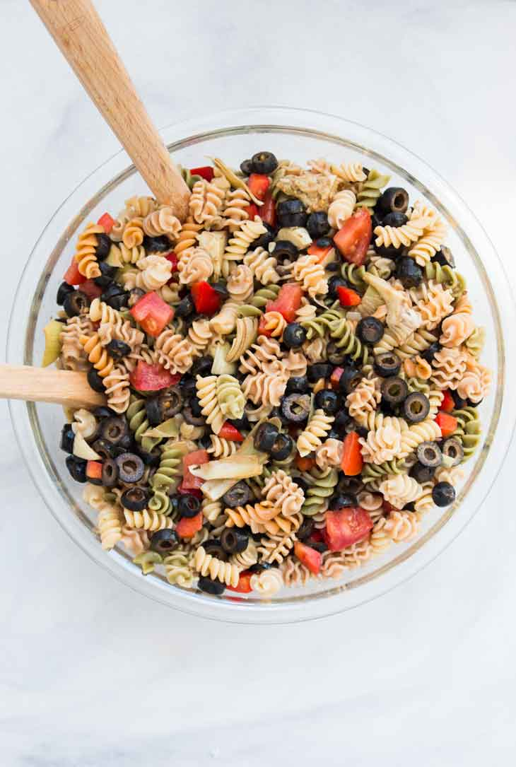 Overhead photograph of a glass bowl containing easy pasta salad recipe with fresh veggies and italian dressing.