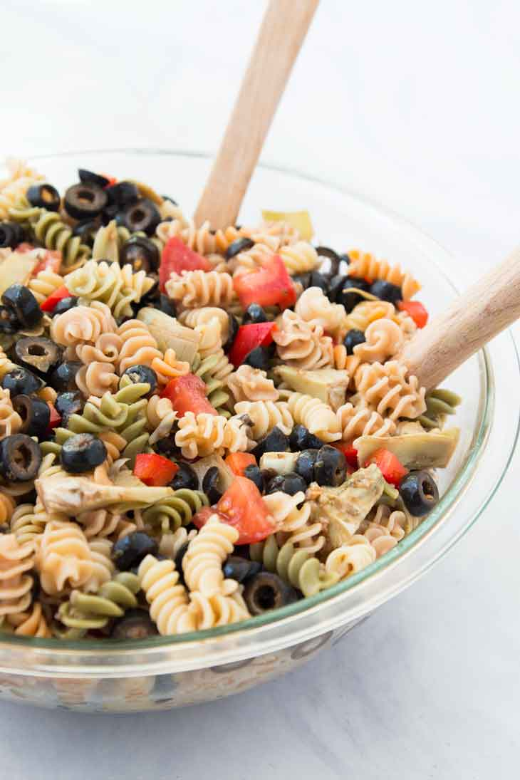 A side close up photograph of easy pasta salad recipe with two wooden spatulas in a glass bowl.