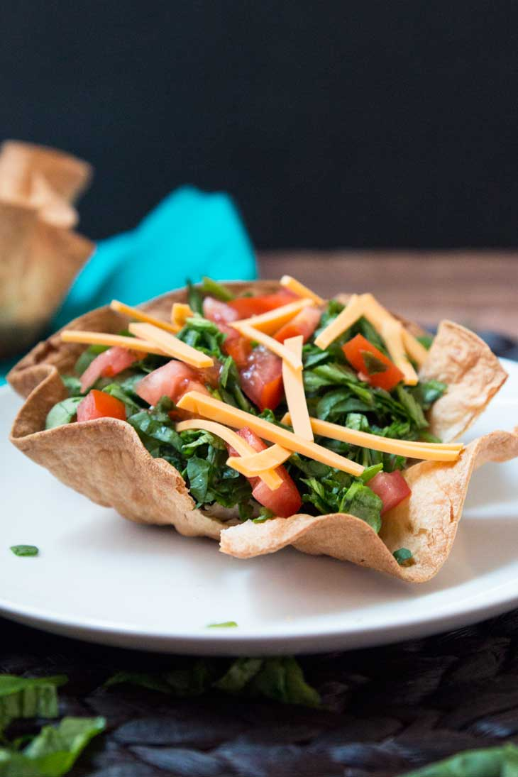 A photograph of a layered taco salad using a baked tortilla bowl. It's filled with black beans, spinach, tomatoes, and cheese.