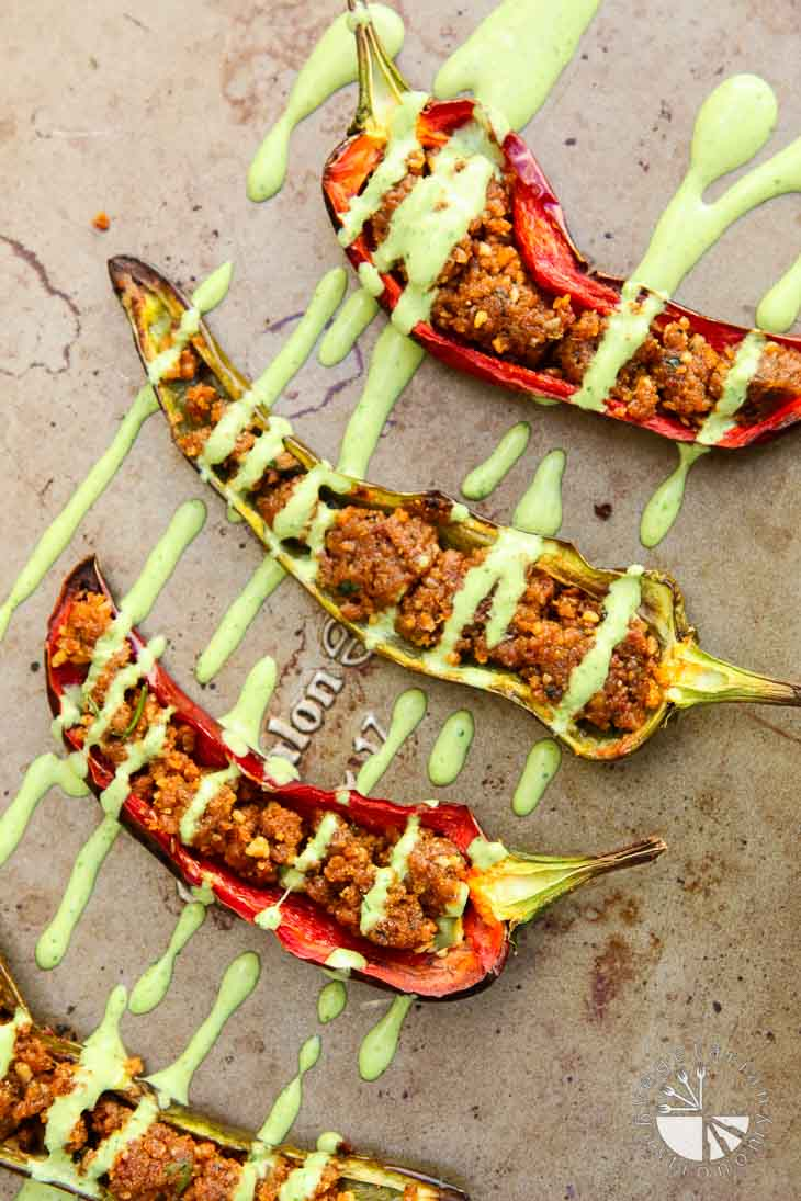 An overhead photograph of stuffed anaheim peppers with cilantro tahini sauce drizzled on top. They are sitting on a baking sheet.