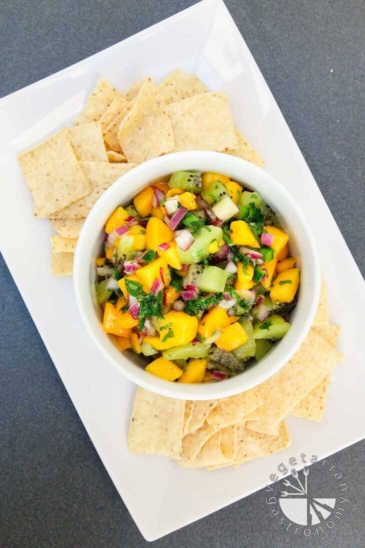 An overhead photograph of a white bowl filled with fresh mango kiwi salsa. It's sitting on a rectangular plate with chips around the side.