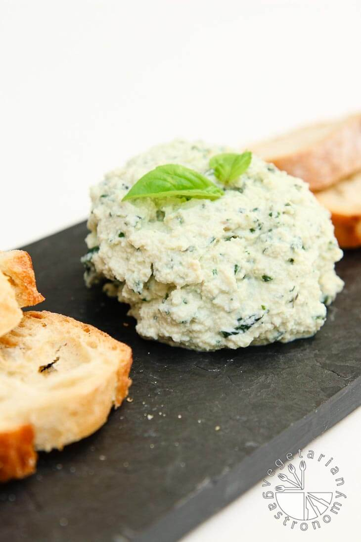 A side view of a small cheese plate consisting of garlic basil vegan ricotta cheese with slices of french bread. It's sitting on a black tray.