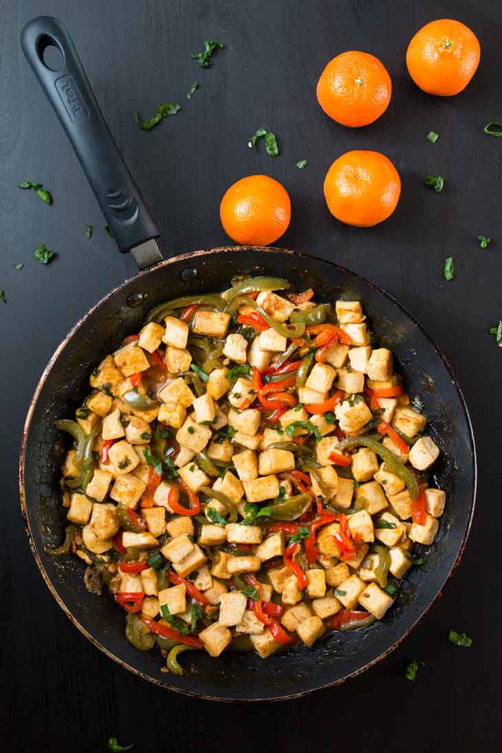 Overhead photograph of orange tofu stir-fry served on a frying pan with three navel oranges off to the side.