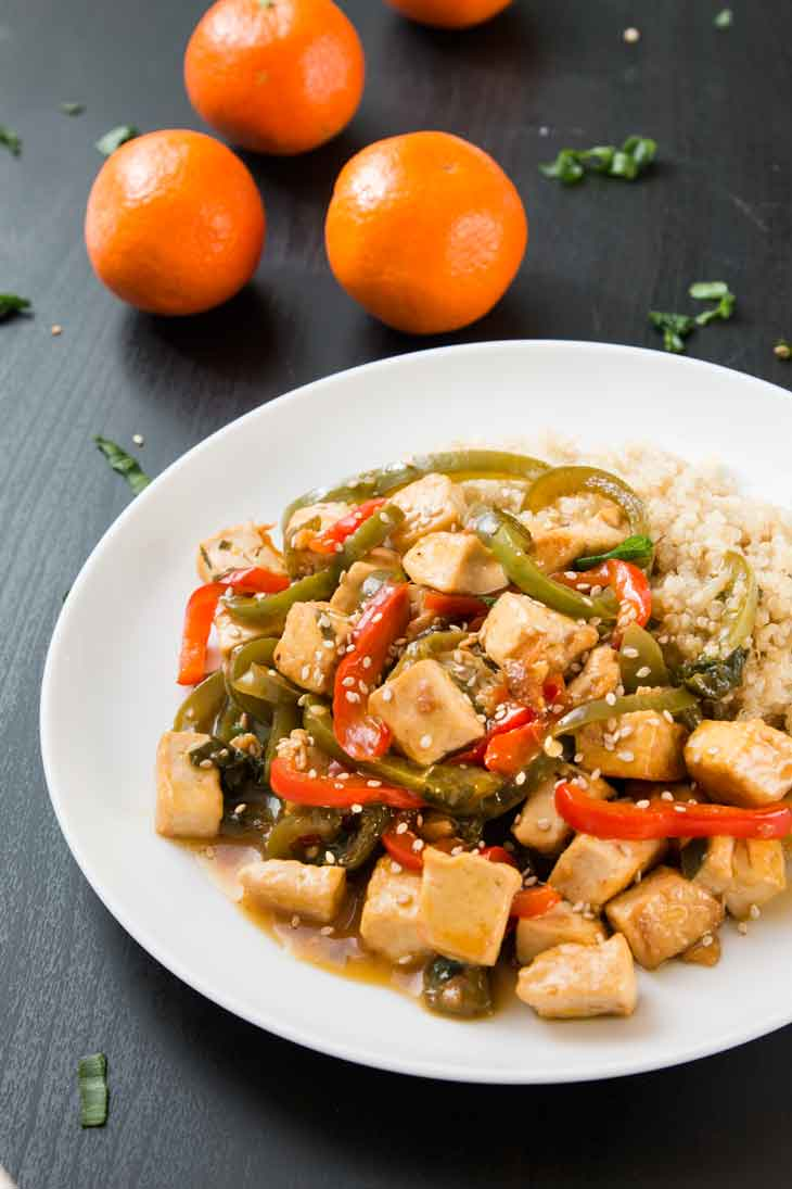 A side photograph of orange tofu stir-fry served over quinoa on a white plate. There are three navel oranges in the background.