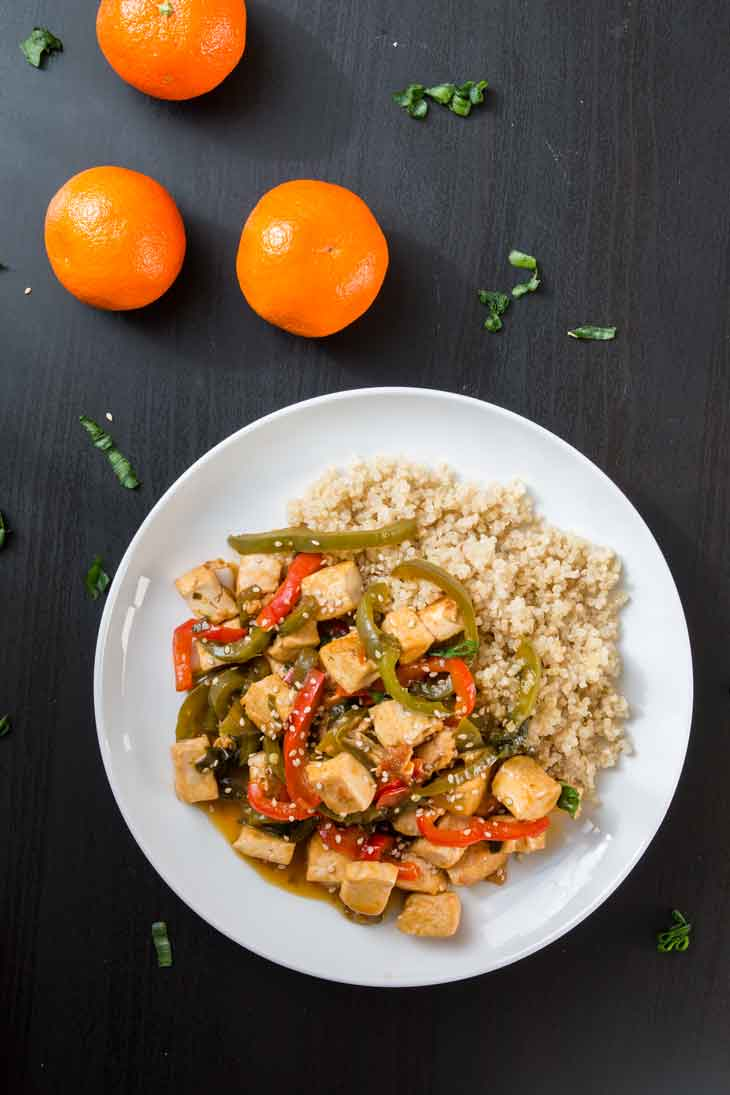 An overhead photograph of orange tofu stir-fry served with cooked quinoa on a white round plate. There are three navel oranges off to the side.
