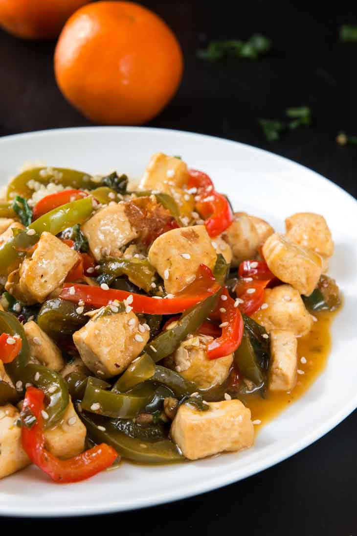 A close-up photograph of orange tofu stir-fry with peppers served on a white round plate. There are navel oranges in the background.