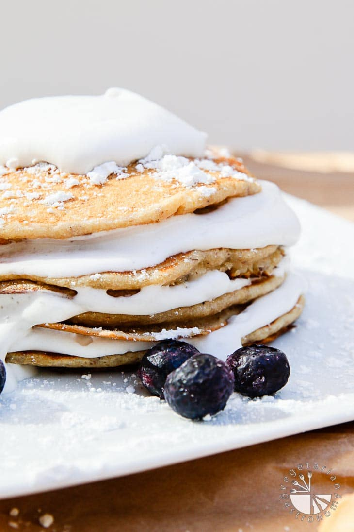 A side view photograph of vegan brunch recipes consisting of banana macadamia nut pancakes with coconut whip cream. There are four pancakes stacked on top of each other with a layer of coconut whip cream in between. It's sitting on a white plate with three blueberries in front for garnish.