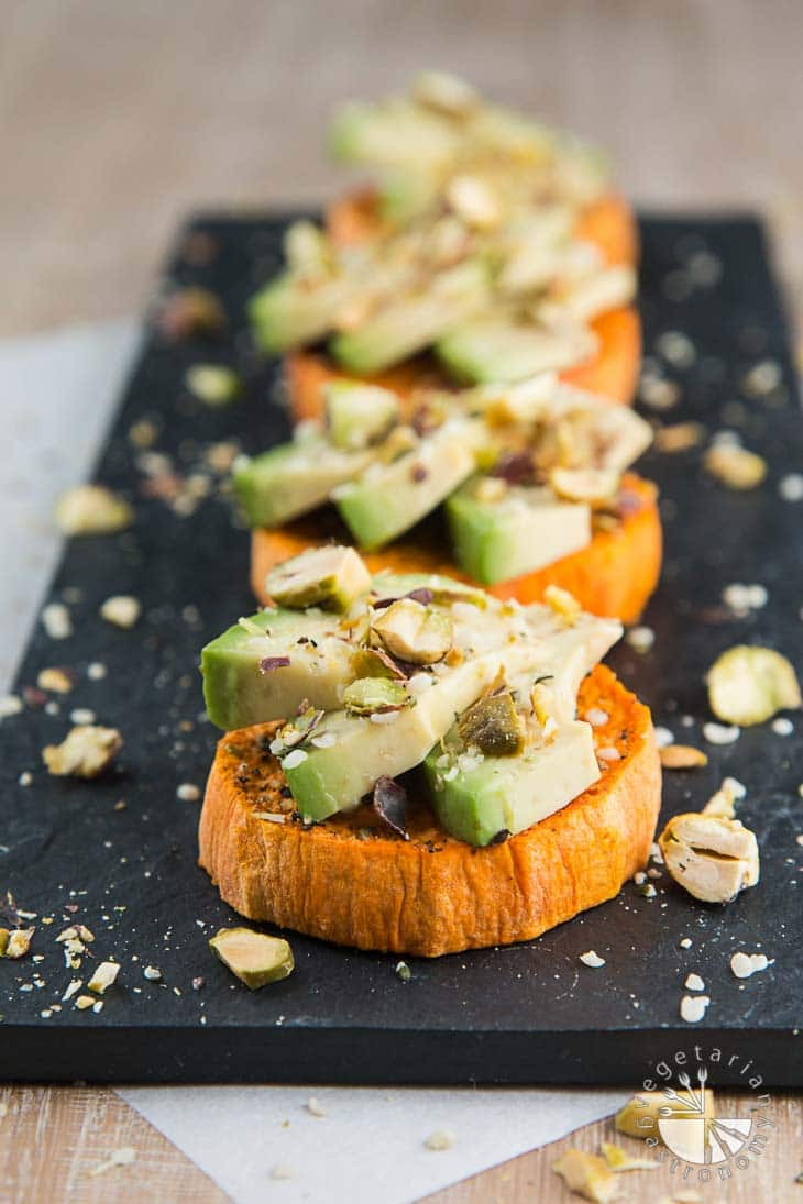 A front view of vegan brunch recipes consisting of four sweet potato avocado toasts topped with hemp seeds and roasted pistachios. The toasts are sitting on top of a rectangular black board, some parchment paper underneath, and a light wooden board. Pieces of roasted pistachios serve as garnish.