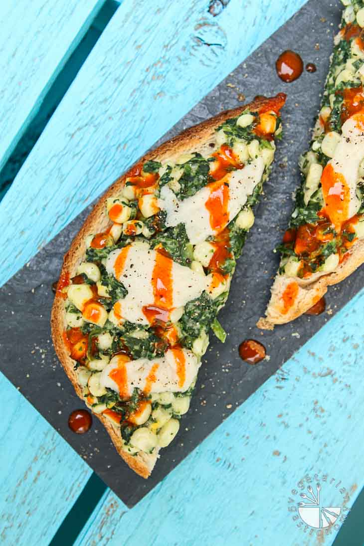 An overhead photograph of vegan brunch recipes consisting of creamy corn and spinach toast with hot sauce drizzled on top. The toast is sitting on a rectangular black tray at a diagonal. The tray is sitting on a turquoise wooden palate.