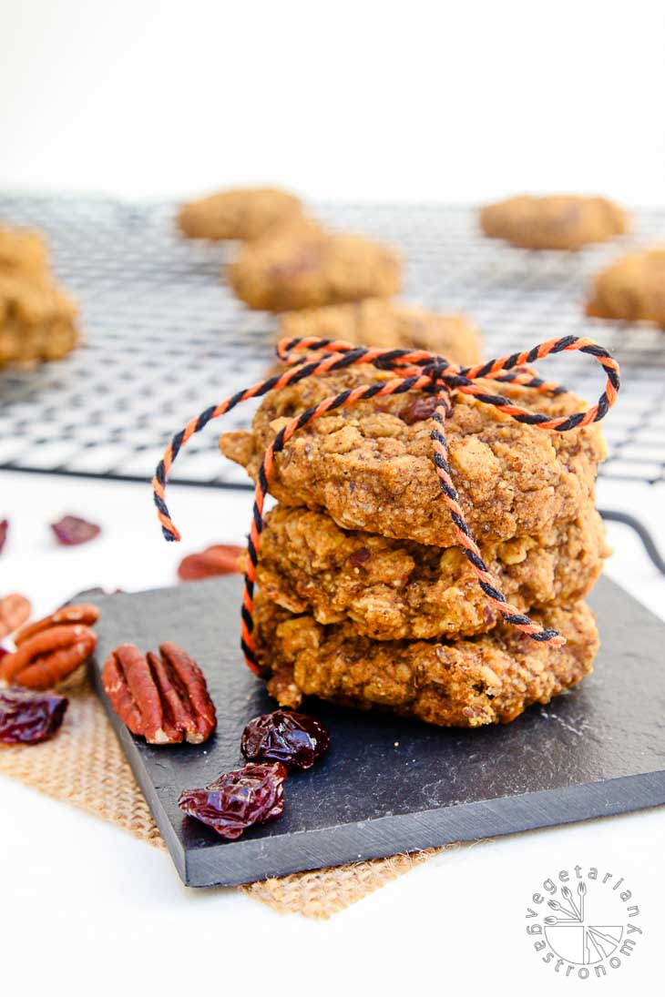 A front view photograph of vegan brunch recipes consisting of pumpkin pecan cookies. There are three stacked cookies tied with an orange black string, sitting on a square black tray, and garnished with pecans and cranberries. There are additional cookies sitting on a cooling rack in the background out of focus.