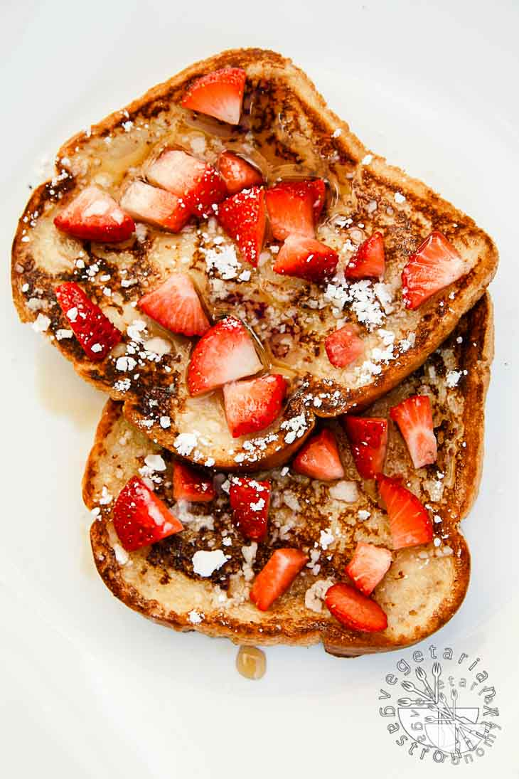 An overhead photograph of vegan brunch recipes consisting of french toast. there are two toasts partially on top of each other, topped with maple syrup, powdered sugar, and diced strawberries. The toasts are sitting on a white background.