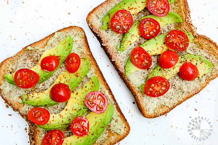 Overhead photograph of vegan brunch recipes consisting of two avocado cherry tomato toasts. They are sitting on a white background and topped with black pepper and salt.