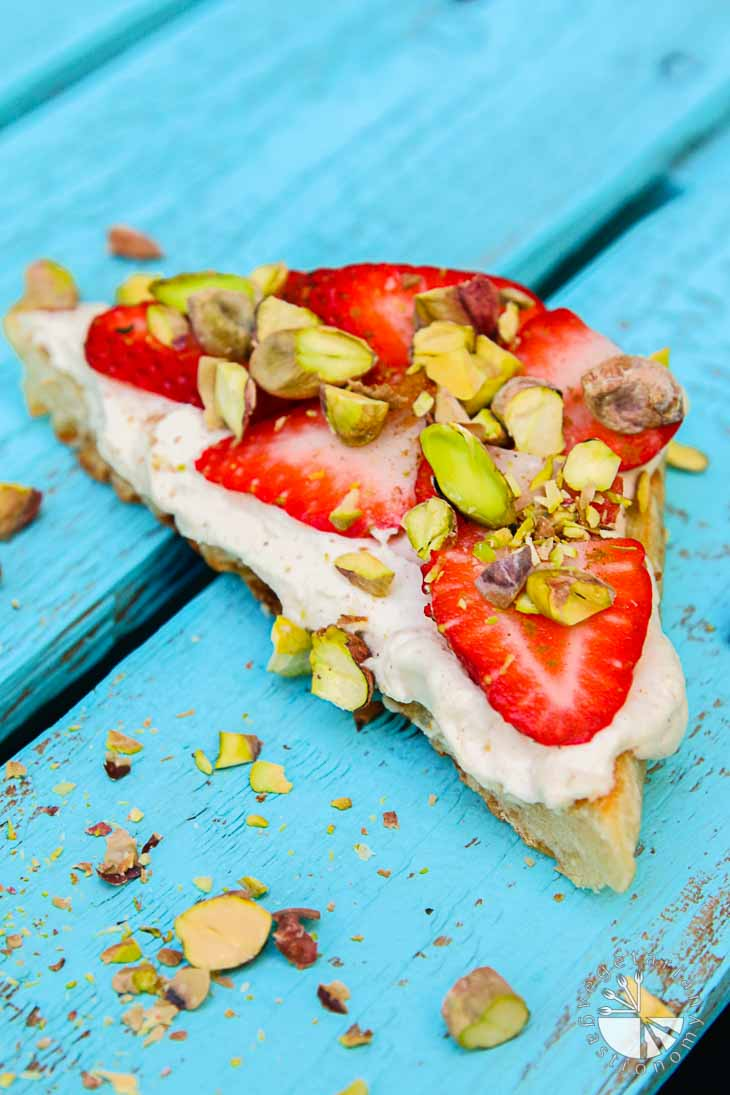 Vegan brunch recipes consisting of cinnamon-infused mascarpone on focaccia topped with strawberries and roasted pistachios. The toast is sitting on a turquoise wooden plank, and garnished with pistachio pieces in front.