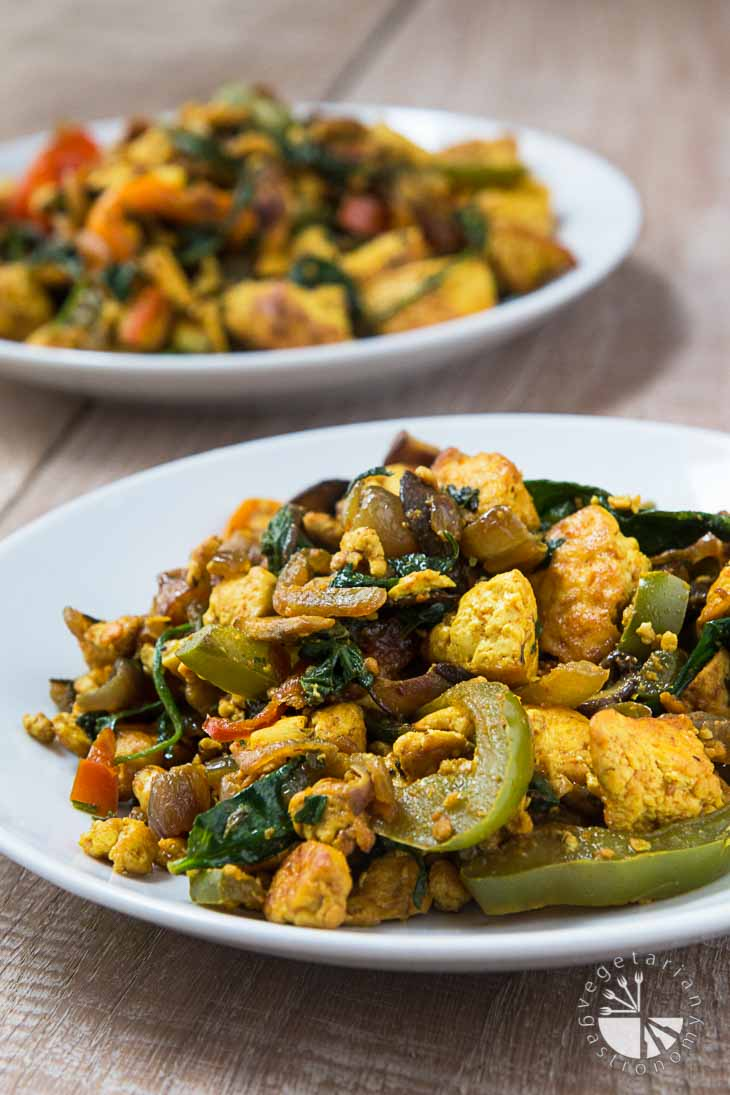 A front view photograph of a white plate containing curried tofu scramble. These vegan brunch recipes consists of a mixture of cooked veggies and pan-fried tofu. There is a second serving out of focus in the background. The plates are sitting on a light wooden palate.