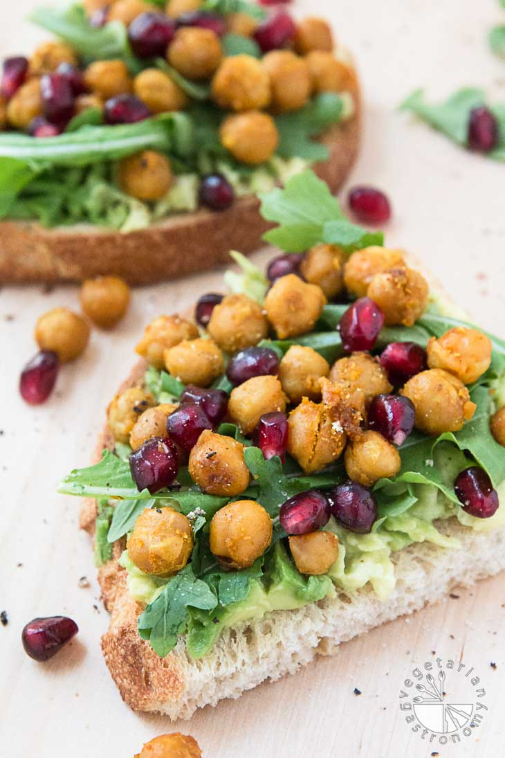 A 45 degree angle photograph of vegan brunch recipes. There is a loaded toast layered with avocado, arugula, roasted chickpeas, and pomegranate seeds. Another serving is out of focus in the background. There are roasted chickpeas and pomegranate seeds on the surface around the toasts for garnish.
