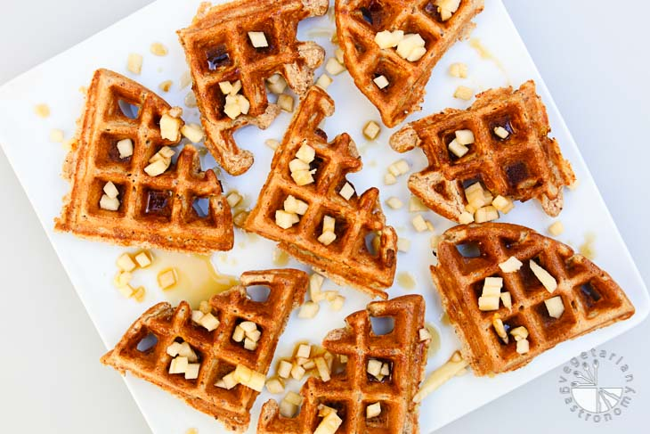 Overhead shot of apple cinnamon waffles cut into quarters and placed on a square white plate. The waffles are topped with maple syrup and diced apples. These vegan brunch recipes are sitting on a white board.
