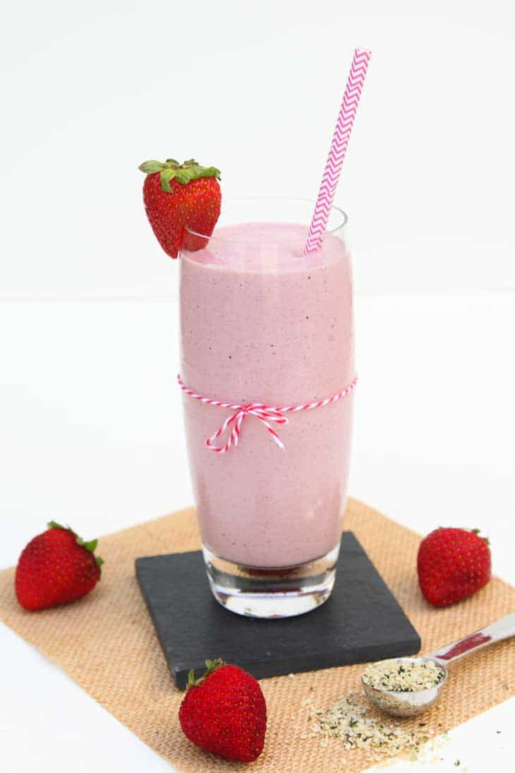 Side photograph of a tall glass of Strawberry Milkshake recipe. There's a pink straw, strawberries, and hemp seeds.