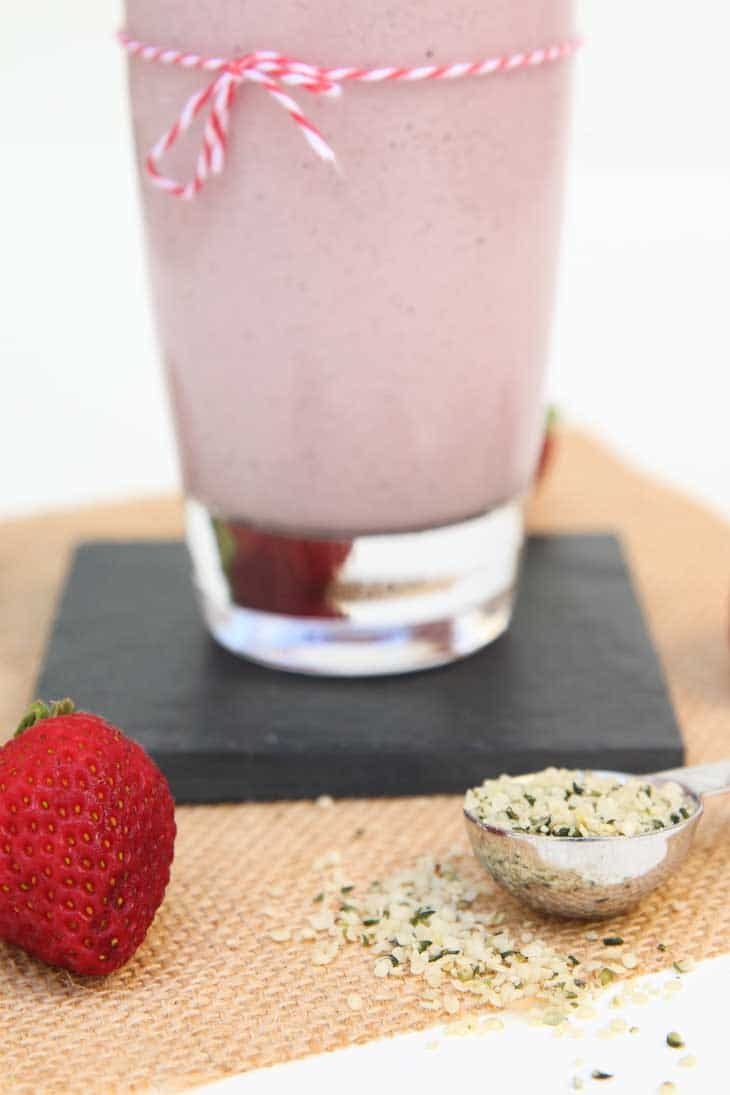 Closeup of hemp seeds and fresh strawberries being used in a vegan strawberry milkshake recipe.