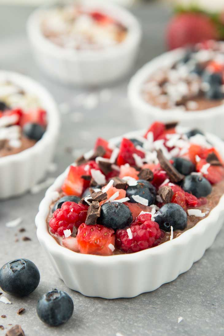 A side photograph of chocolate chia pudding topped with fresh berries, coconut, and chocolate. There are some additional servings in the background.