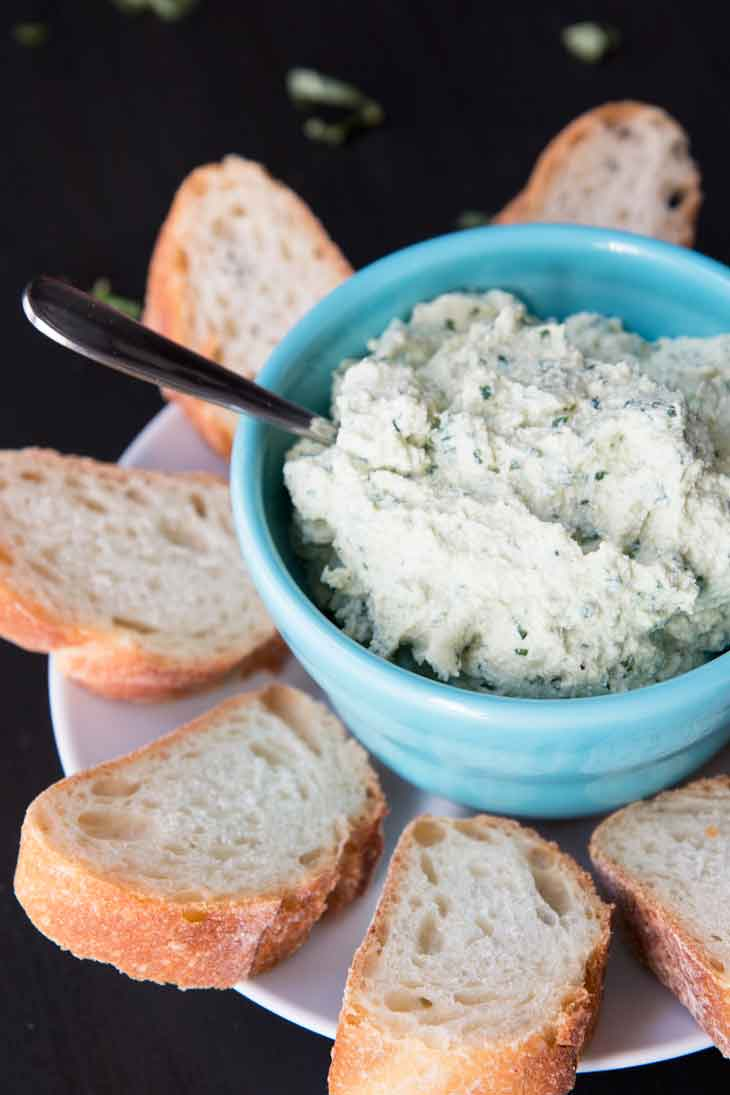 Side photograph of vegan tofu ricotta spread plated in a blue bowl and surrounded by slices of french bread.