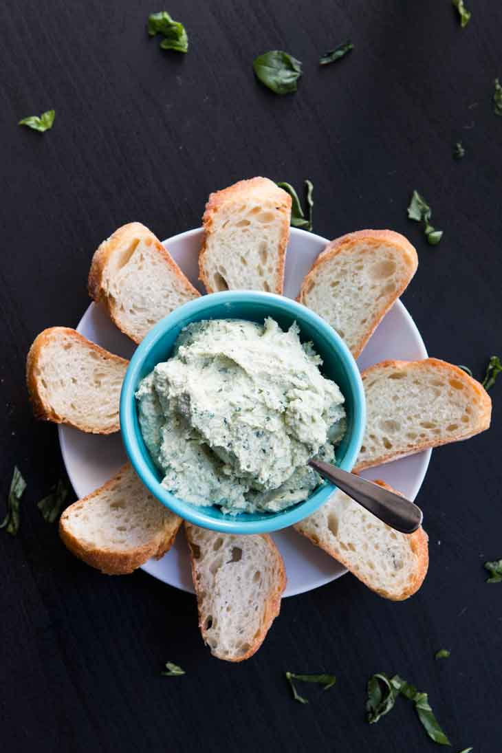 Overhead photograph of vegan tofu ricotta. It's plated in a light blue bowl and served with slices of french bread.