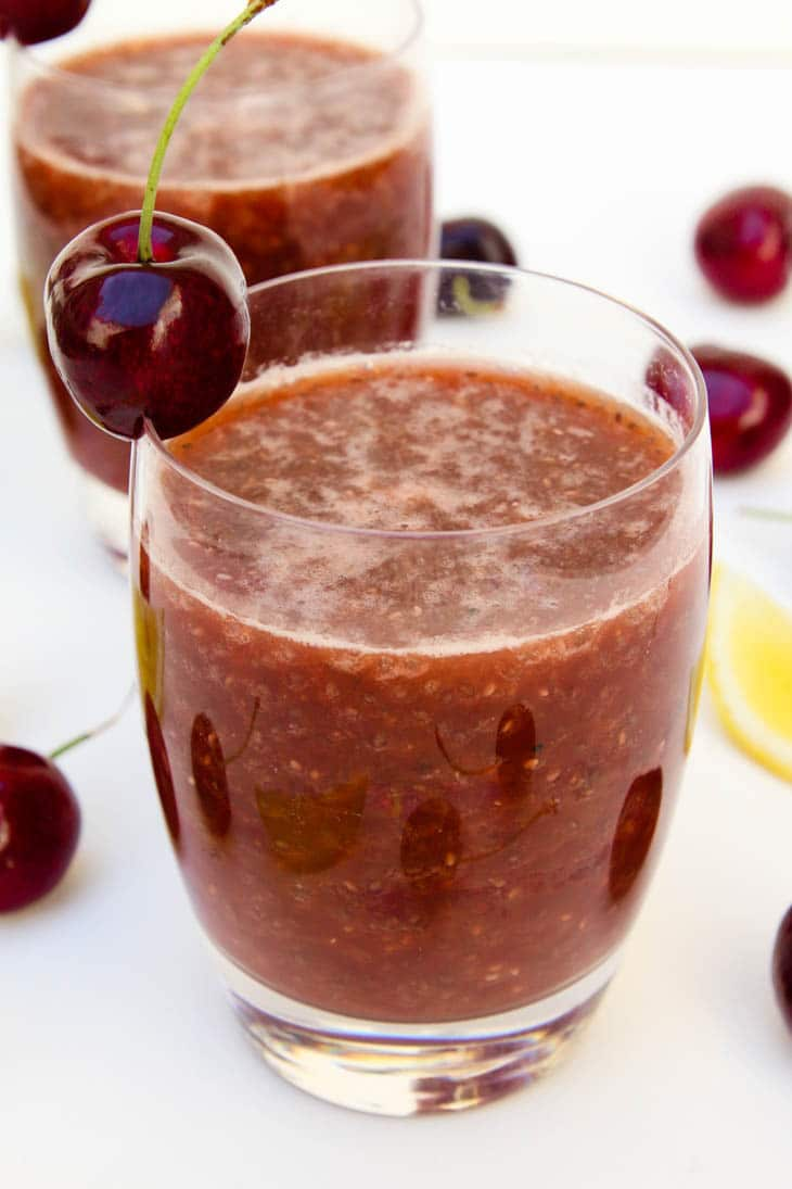 A close up of cherry chia fresca garnished with cherries