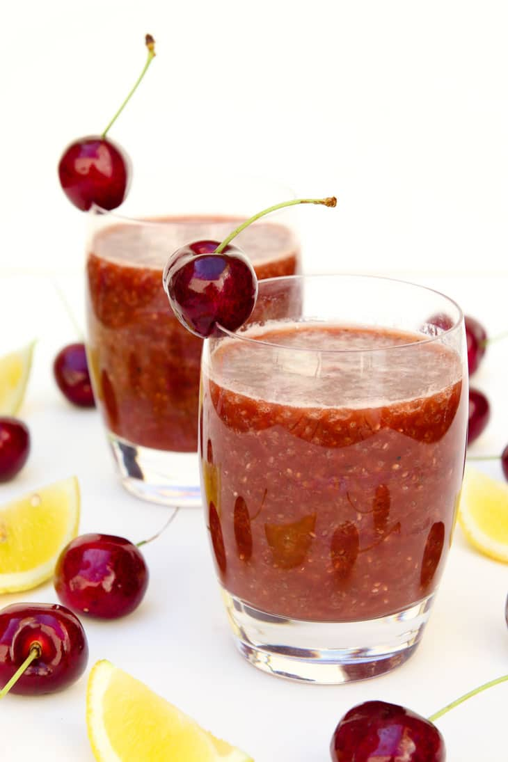 Two glasses of cherry chia fresca garnished with cherries