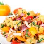 A side shot of a tuscan panzanella salad with white beans on a white plate