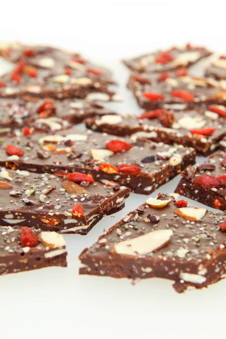 A close up of dark chocolate bark broken into pieces on a white surface