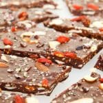 A close up of dark chocolate bark topped with fried berries, nuts and seeds