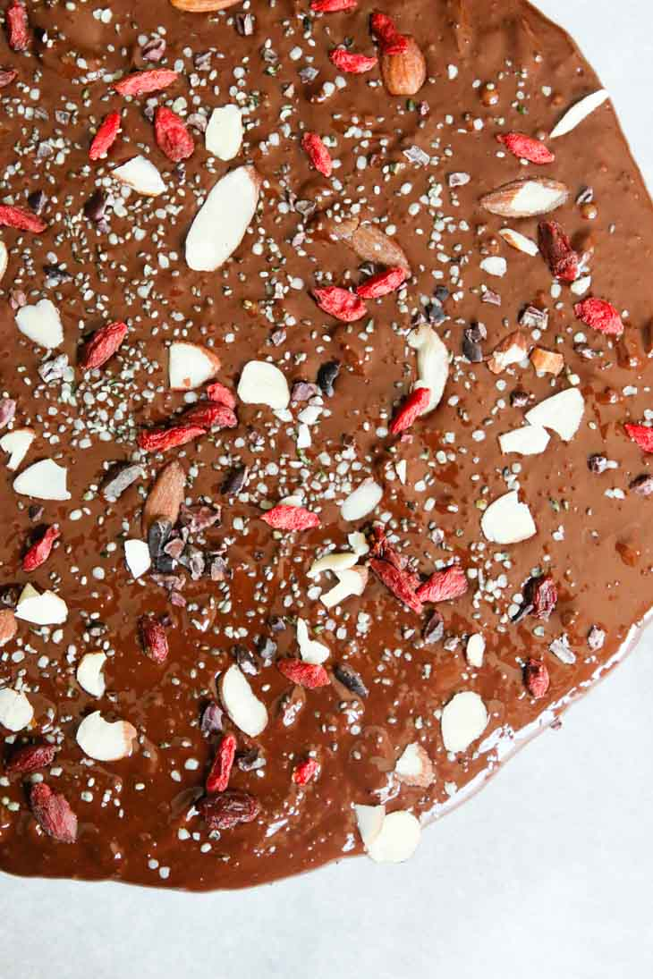 An overhead shot of dark chocolate bark covered in nuts and seeds
