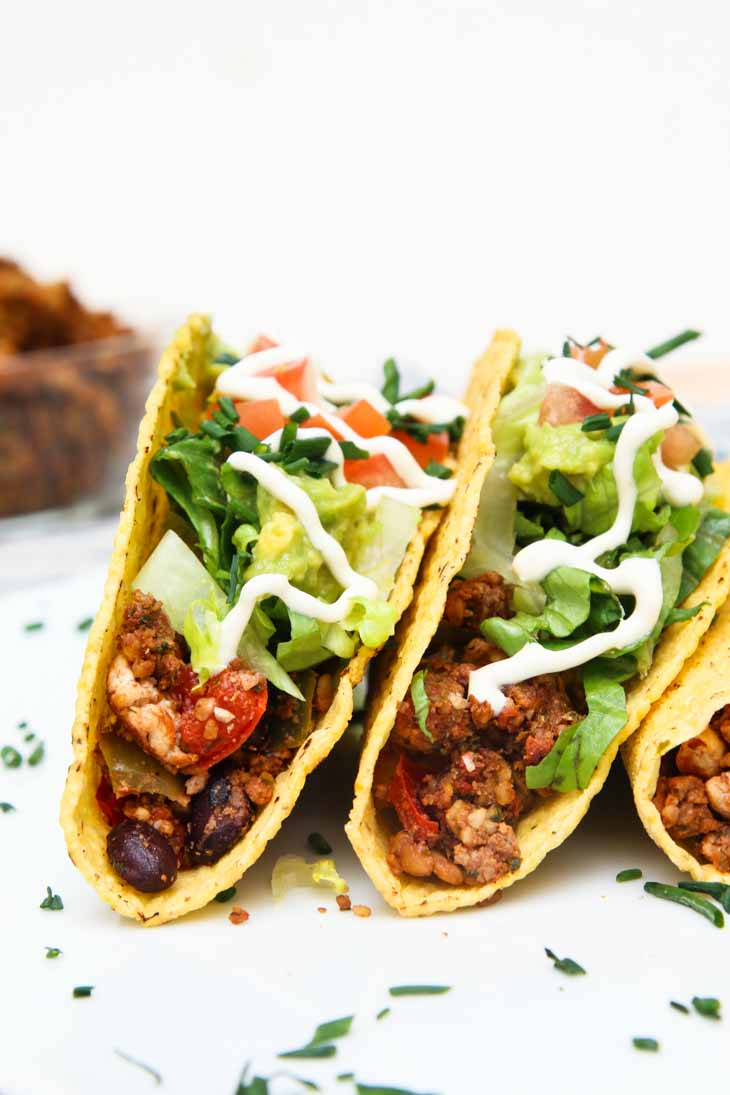 A side close-up photograph of two vegan black bean tofu tacos garnished with cilantro.