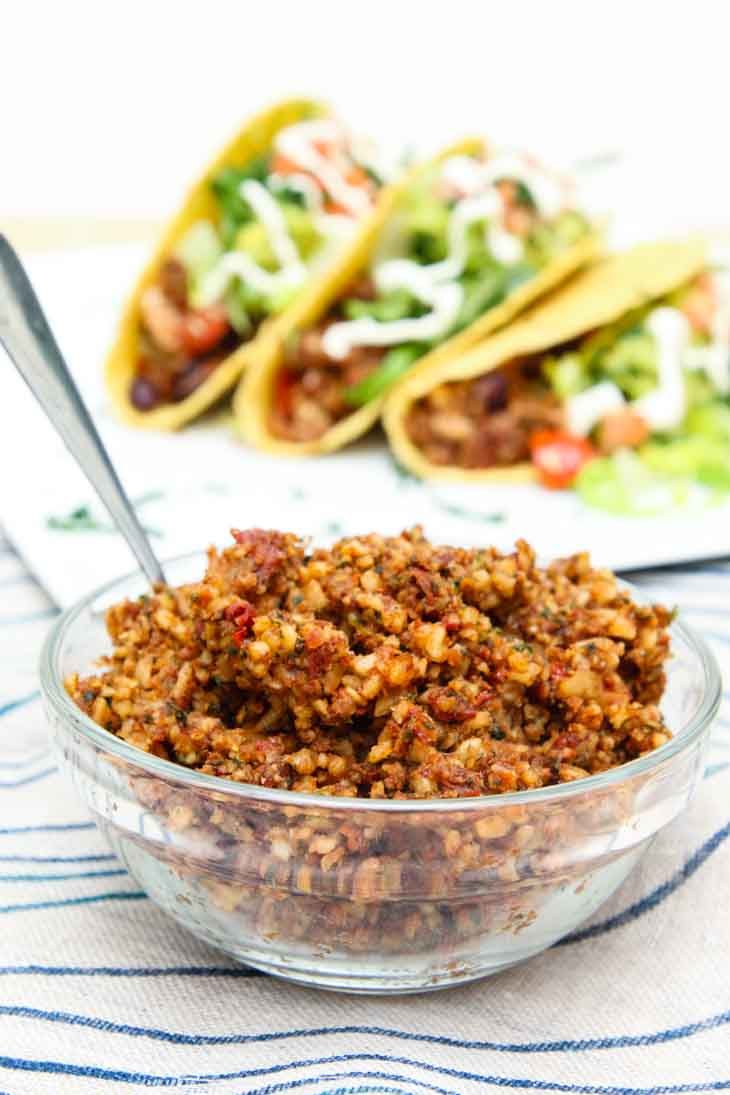 """""""Meatless"""" sun-dried walnut vegan crumble in a glass bowl with loaded tofu tacos assembled in the background."""