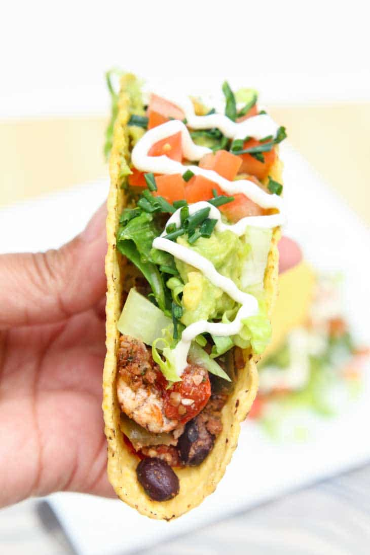 A side close-up photograph of a person holding a vegan tofu taco.