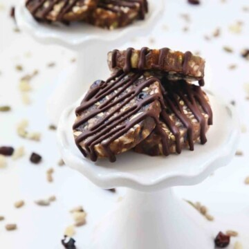 Portrait size image of No-Bake Chewy Chocolate Date Cookies. They are made with dates, seeds, and dried fruit, with chocolate drizzled on top. The date cookies are allergen-friendly and are gluten-free, dairy-free, soy-free, eggless, and vegan. They are sitting on a white cupcake stand with the seeds and dried fruit mixture sprinkled around it.