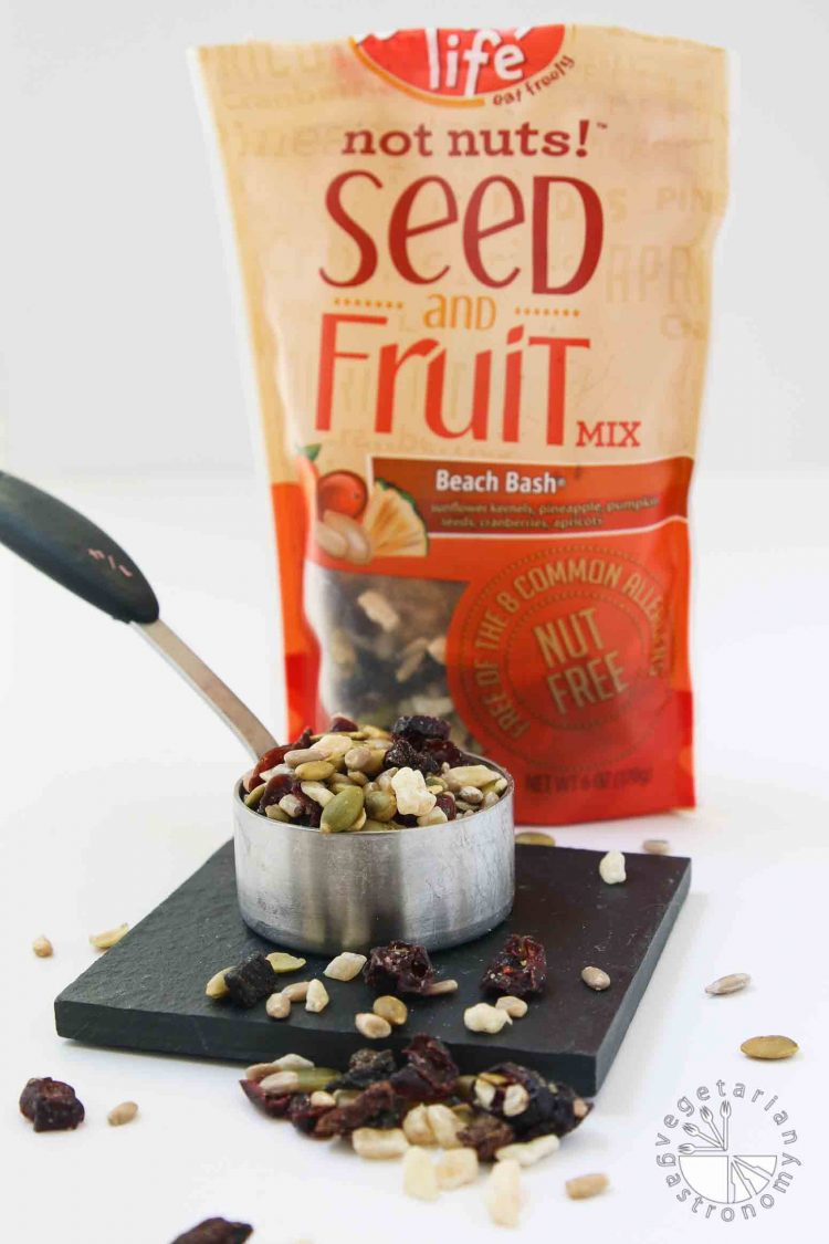 This picture of Enjoy Life Beach Bash seed and dried fruit mixture. the seed and dried fruit mixture used in my No-Bake Chewy Chocolate Date Cookies. The mix is sitting in a measuring cup with the bag behind it. It's soy-free, nut-free, gluten-free, and vegan.