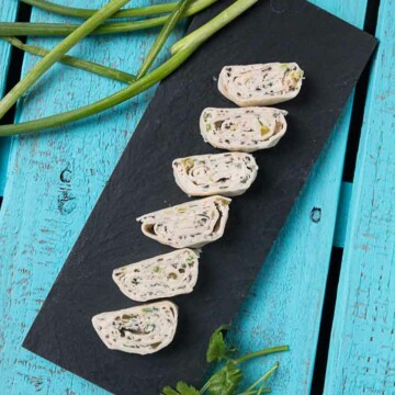 An Overview Shot of Six Vegan Mexican Tortilla Pinwheels Made with Cream Cheese. The Tortilla Pinwheels are Sitting on Top of a Black Rectangular Plate with some Green Onions and Cilantro off to the side for Garnish. The Backdrop is a Wooden Turquoise Palate.