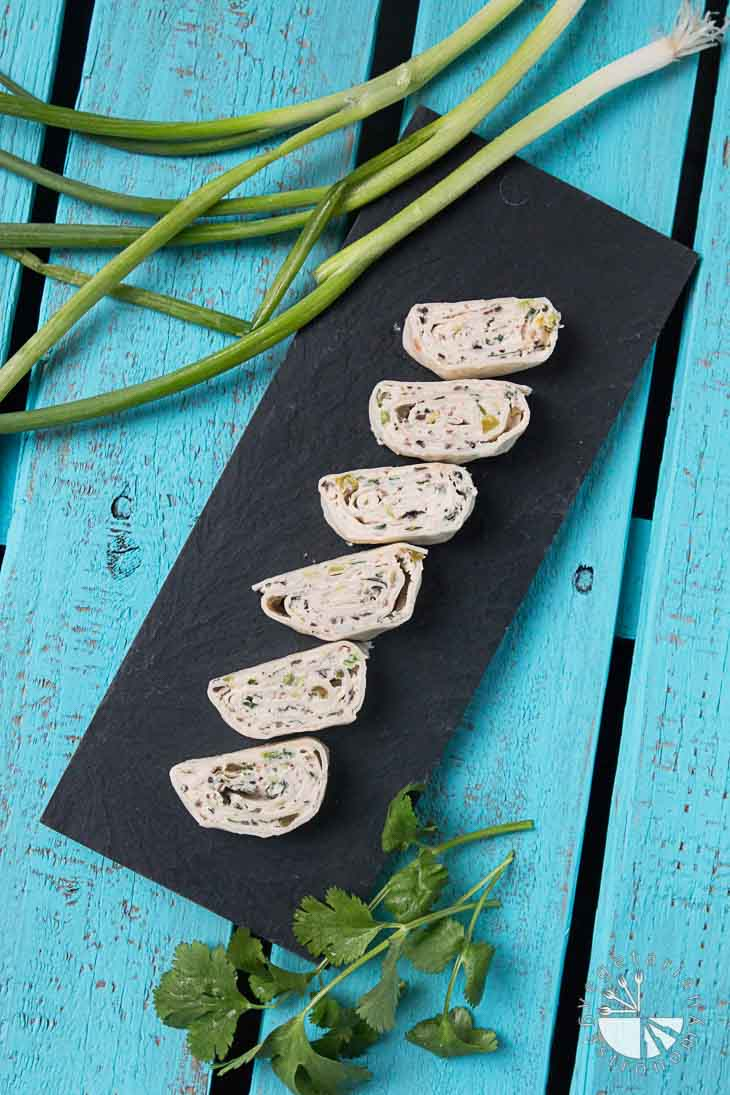 An Overview Shot of Six Vegan Mexican Tortilla Pinwheels with Cream Cheese on a Black Rectangular Plate with a Green Onions and Cilantro Garnish. The Backdrop is a Wooden Turquoise Palate.