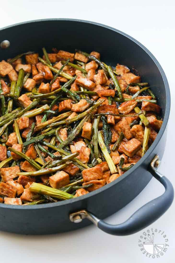 A side 45 degree partial view of a large non-stick black pan containing Teriyaki tofu stir fry with asparagus.