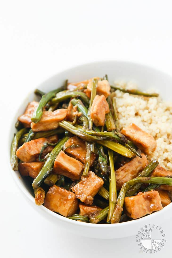 Front photograph of a white bowl containing Teriyaki Tofu stir fry with asparagus and cooked quinoa.