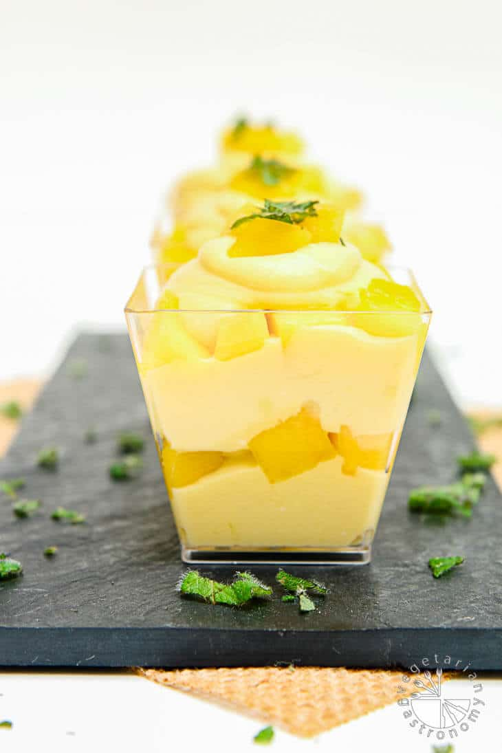 A front photograph of mango mouse parfait in square glass cups sitting on a black palate. There's mint around the sides as garnish.
