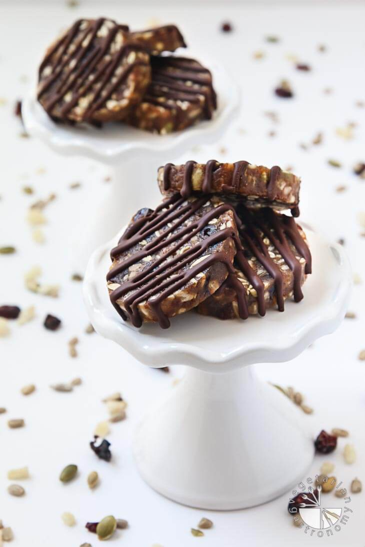A side photograph of no-bake date cookies. There are 2 sets of 3 cookies on a white holder with nuts and dried fruit scattered around.