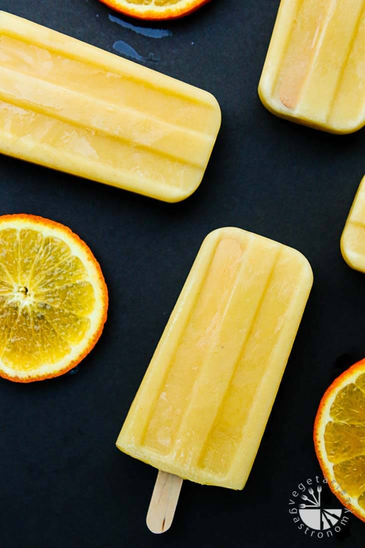 An overhead photograph of orange julius popsicles with slices of orange around the sides.