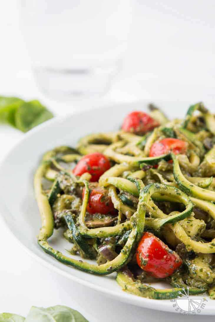 A side photograph of spiralized pesto zucchini spaghetti with tomatoes and mushrooms on a white plate.