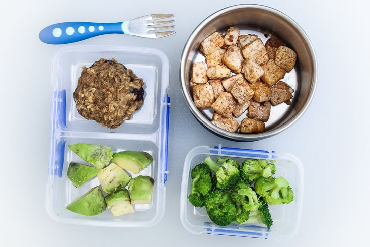 Overhead photograph of easy school lunch idea consisting of cinnamon tofu, steamed broccoli, avocado, and breakfast cookies.