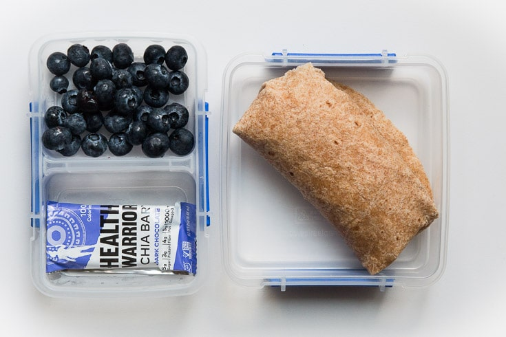 Overhead photograph of easy school lunch idea consisting of blueberries, bean burrito wrap, and chia bar.