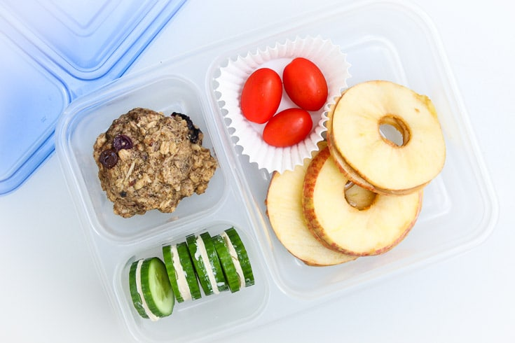 Overhead easy school lunch idea consisting of apple nut butter sandwiches, grape tomatoes, cookies, and cucumber hummus sandwiches.