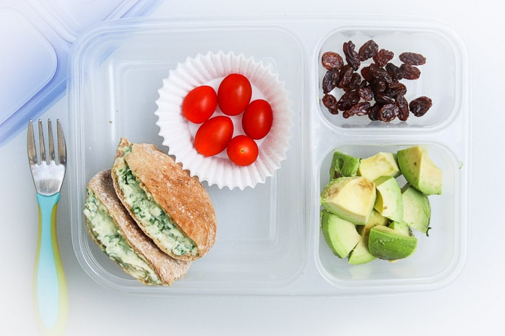 Overhead photograph of easy school lunch idea consisting of mini pita pockets, grape tomatoes, raisins, and avocado.