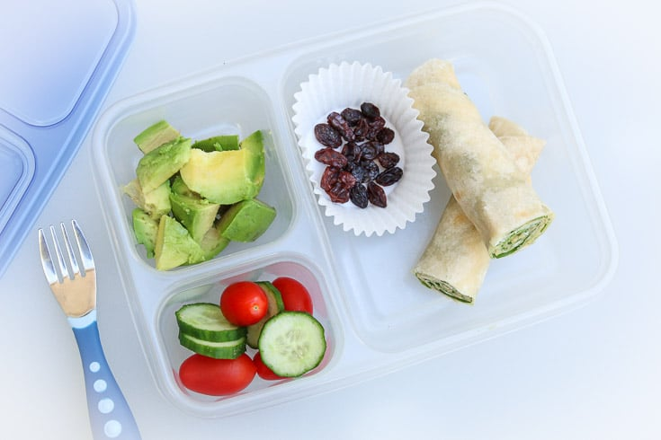 Overhead photograph of easy school lunch idea consisting of cream cheese spinach roll-ups, raisins, avocado, and raw veggies.